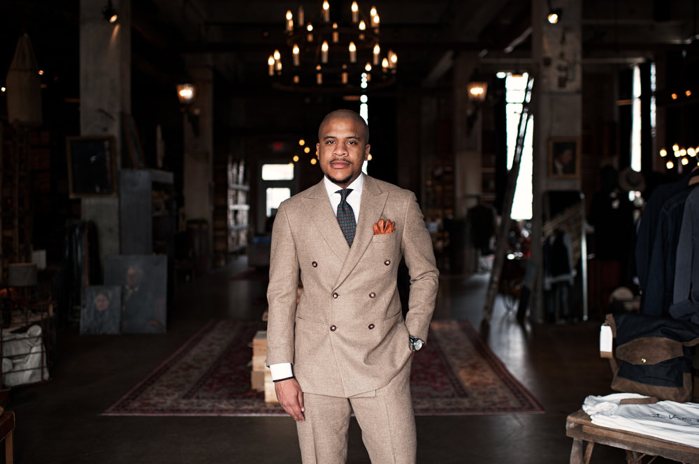 man in a bespoke classic tan suit with wide lapel and leather gloves in breast pocket