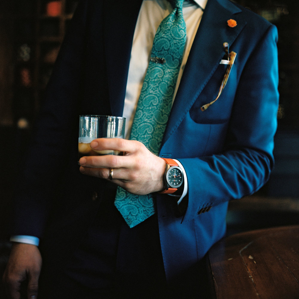 custom navy suit with classic mens accessories: turquoise paisley tie and orange hook and gaff sportfisher watch