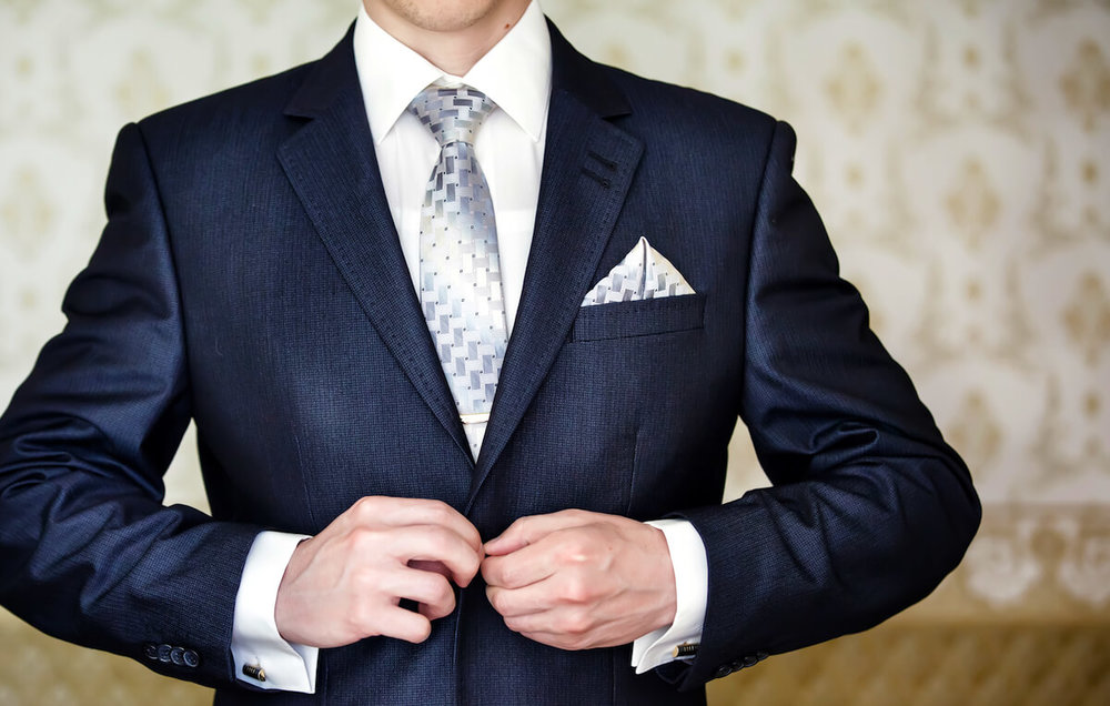dark navy suit with pocket square in winged fold