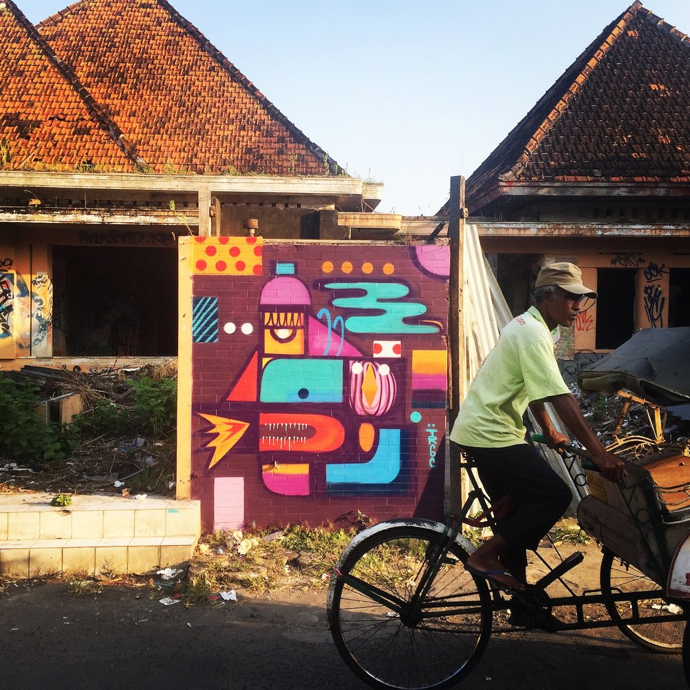 A pedicab passes an abandoned building damaged by the 2006 earthquake, adorned with street art