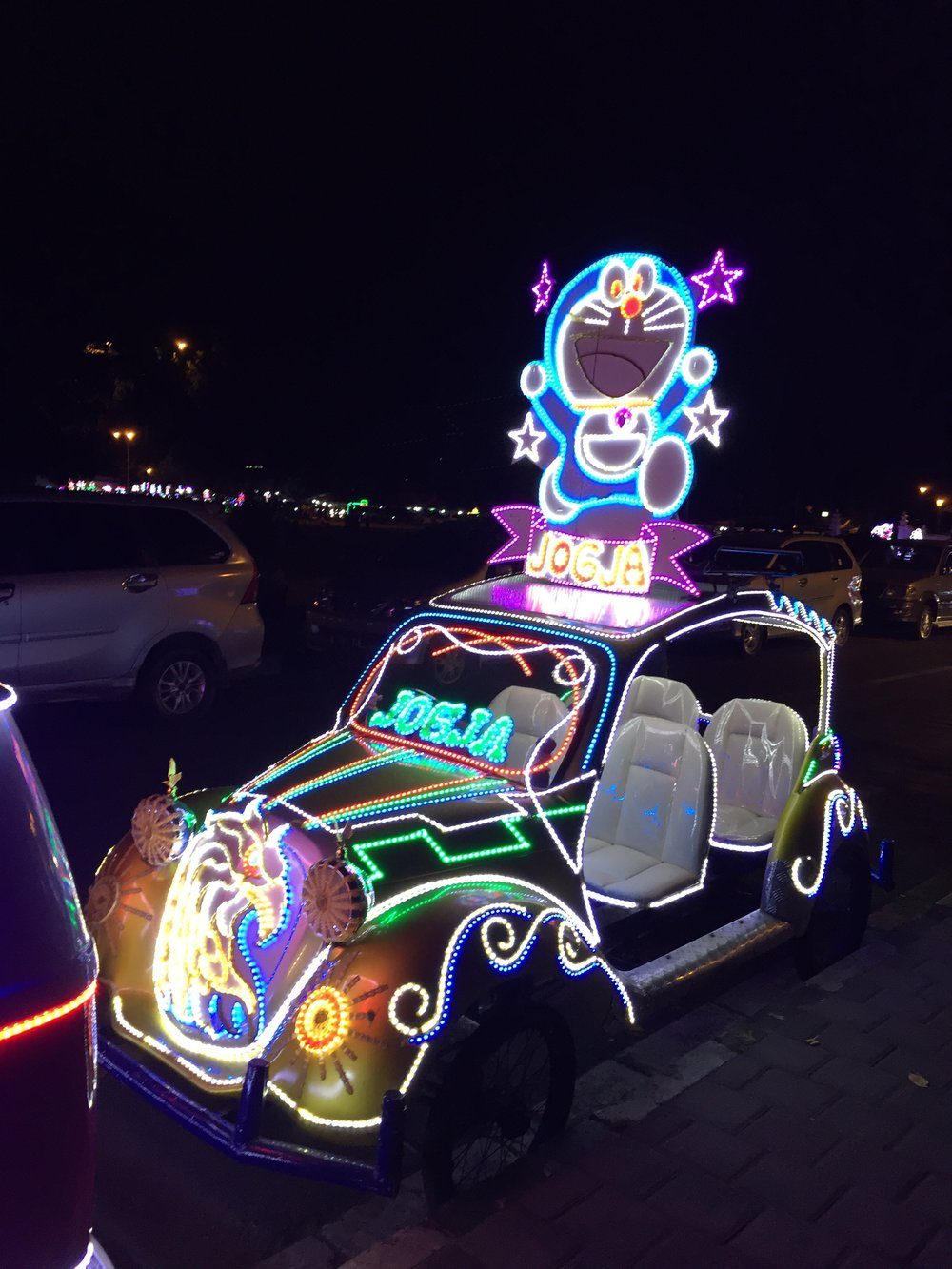 Popular Cultural Expressions.  One of a number of pedicabs, modified with neon, sound systems and other accessories which families use when enjoying a public space Alun Alun.