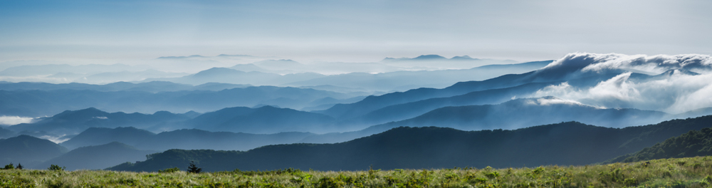 Torn Paper Mountains Standing on top of Round Bald in the Roan Highlands of Tennessee I saw this view.  This image is one of the first panoramas that I shot while hiking and I really wasn't sure if it would work.  I just knew that a small photo of the clouds creeping over the mountains on the right side could never capture the grandeur of the scene. The mountains in the Blue Ridge always remind me of the ragged edge of torn construction paper layered behind each other.