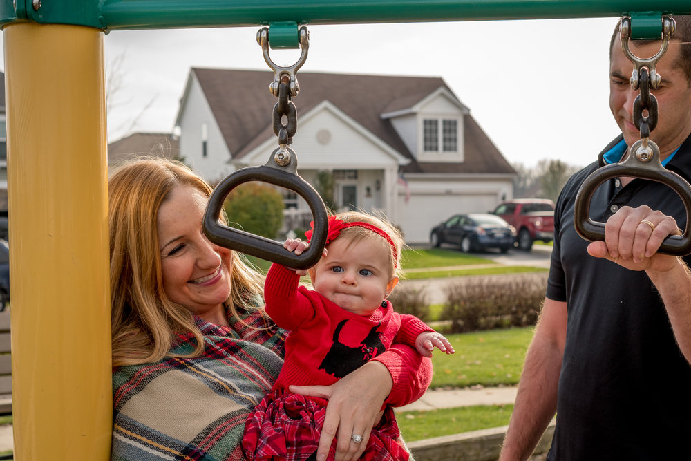 A mother, father, and baby daughter play on the playground for a family session in Antioch Illinois