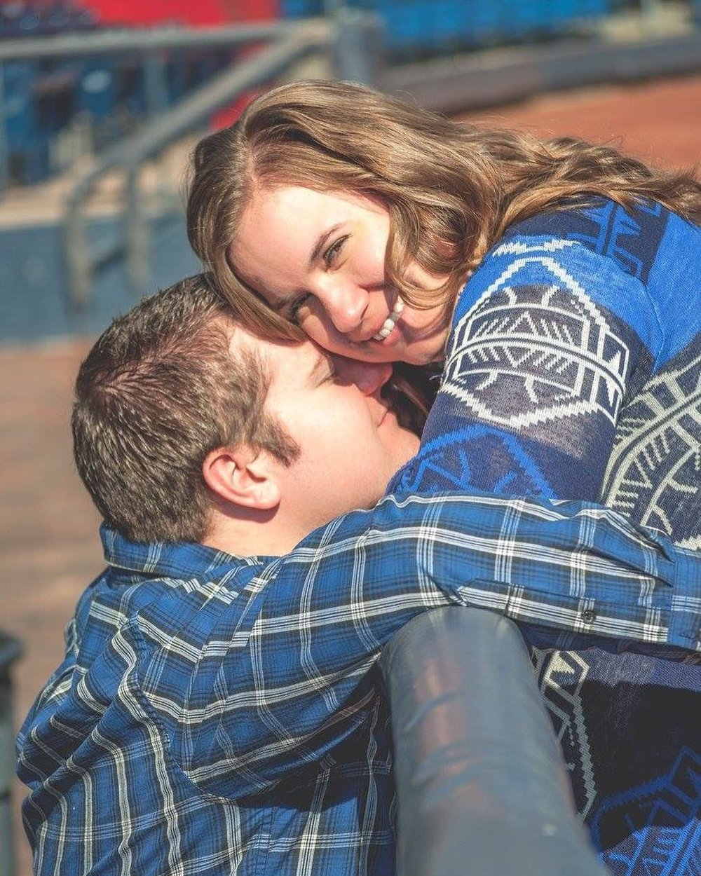 A man in blue kisses a woman in blue in the baseball dugout at Modern Woodmen Park