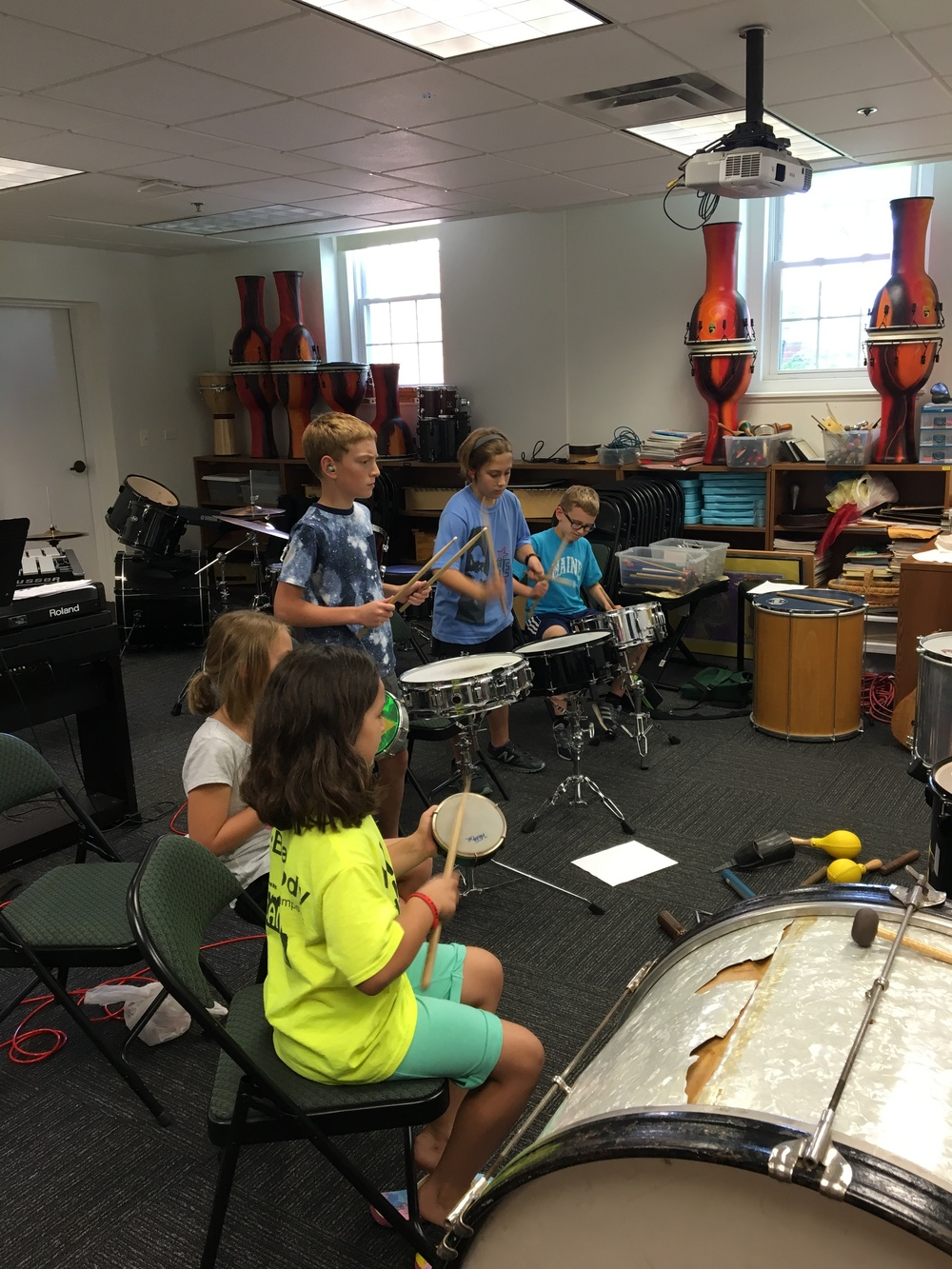 Campers learning to play the drums in music camp