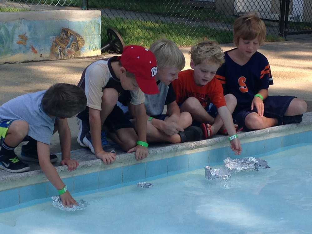 Campers building floating boats using the S.T.E.M. approach.