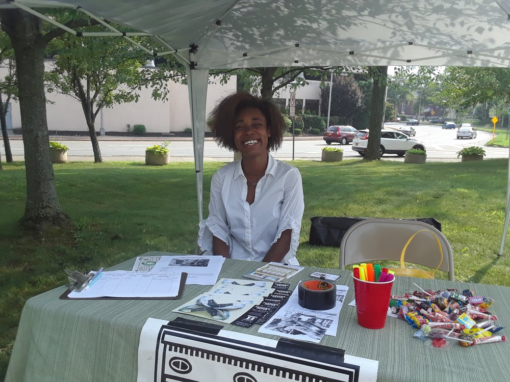 Summer 2018 Intern, Sekaya Newsome working the outreach table at a community event.