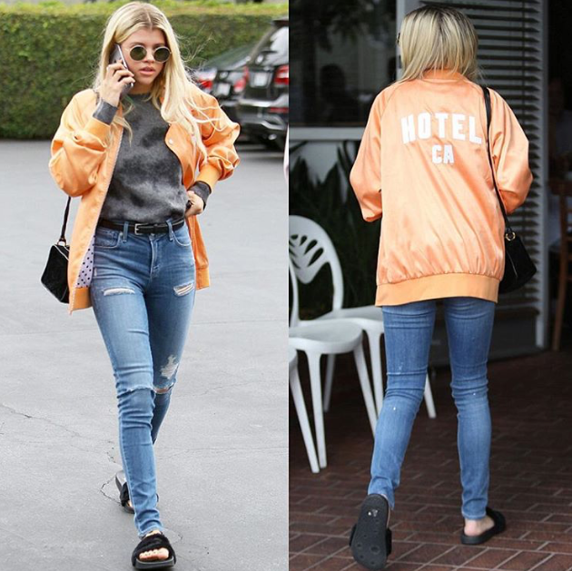 Sophia Richie pairs the black fenty slides with an orange bomber and jeans