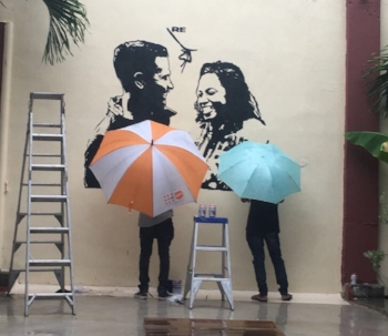 Local artists invited to The Asian Foundation for a cultural event finish mural promoting gender equality in the rain.