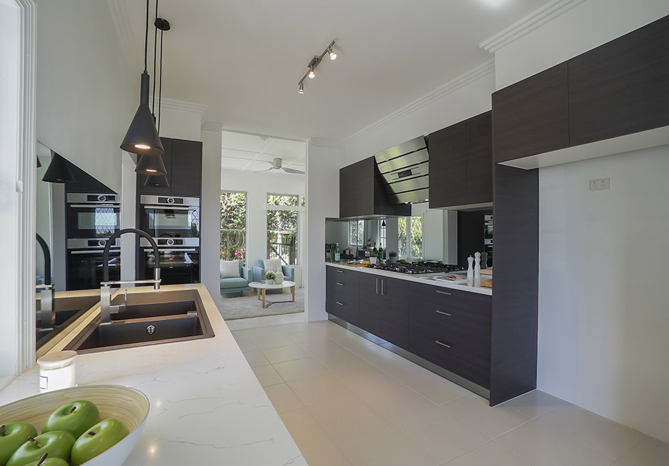 Real estate marketing photography of spacious kitchen with walk-through to external glass doors to a private garden. The professional lighting used in this photograph captures both space and lightness of this beautiful home.