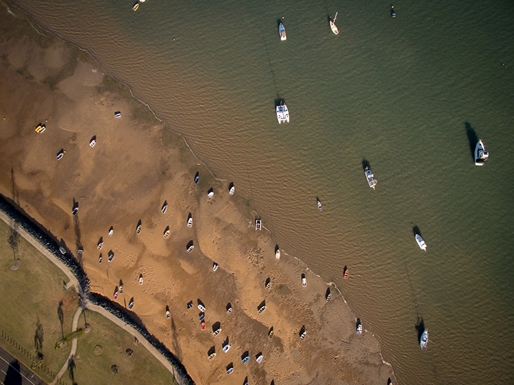 Drone photography of boats on mudflats on Moreton Bay, Brisbane, with more boats on the green-brown water.