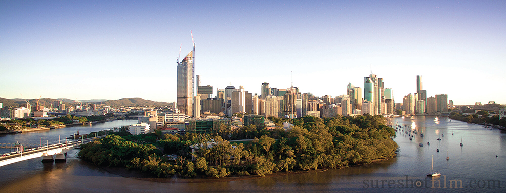 Drone aerial photography of Brisbane city, with boats on the river with trees and gardens on the foreshore.