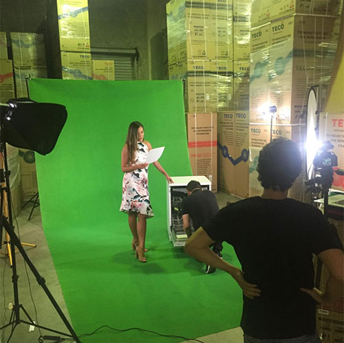 Using a green screen for an advertising video production. A woman holding a script with a dishwasher, and other crew in the back and foreground.