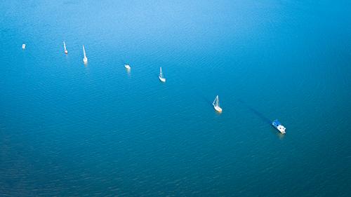 A row of yachts on a blue sea.