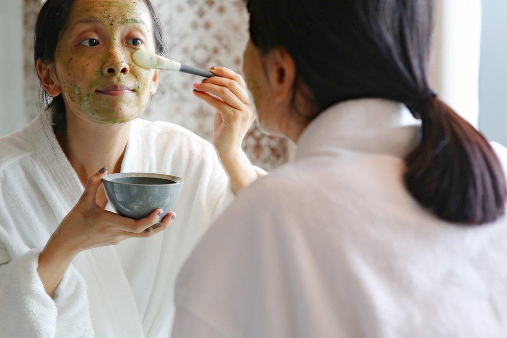 Applying Origins Matcha Madness powder face mask onto my face
