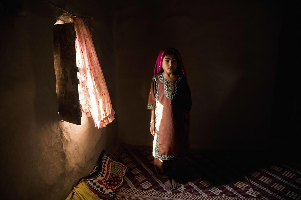 11-åriga Shaneela står vid ett fönster i familjens hem, som består av ett rum, i byn Muhammad Ali Bhar. Hennes föräldrar låter henne inte gå i skolan, men hon smyger ofta in i klassrummet på skolan ändå. Hennes föräldrar säger att de kommer låtahenne gå till skolan så snart det finns tillgång till vatten och en fungerande, separat toalett för flickor. 11-year-old Shaneela stands by a window inside her one-room home in Muhammad Ali Bhar. Her parents do not allow her to attend school, although she often sneaks into the classroom anyway. Her parents say they will send her to school when there is access to water and a separate functioning toilet for girls.