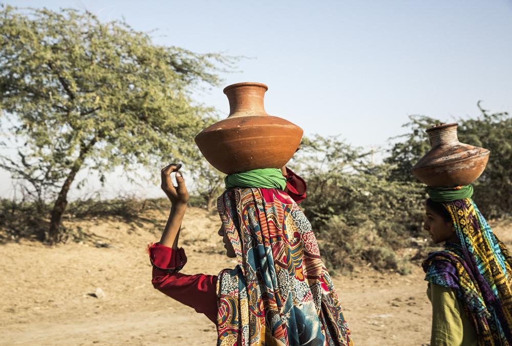 Kvinnor hämtar vatten med traditionella lerkrukor i den öppna kanalen i Noor Muhammad Thaheem, som transporterar dricksvatten från Keenjharsjön till Karachi. Den lokala regeringen ger inte byborna tillstånd att ansluta en rörledning från kanalen till byn, eftersom de är rädda att vattentillförseln till Karachi, som redan lider av vattenbrist,ska minska. Women collect water in traditional terracotta pots from the open canal in Noor Muhammad Thaheem. The canal transports drinking water from Keenjhar Lake to Karachi, however the local government will not allow the village residents to connect a pipe from the canal to their community, because they fear that the water supply to Karachi, which already suffers water shortages, will be reduced.