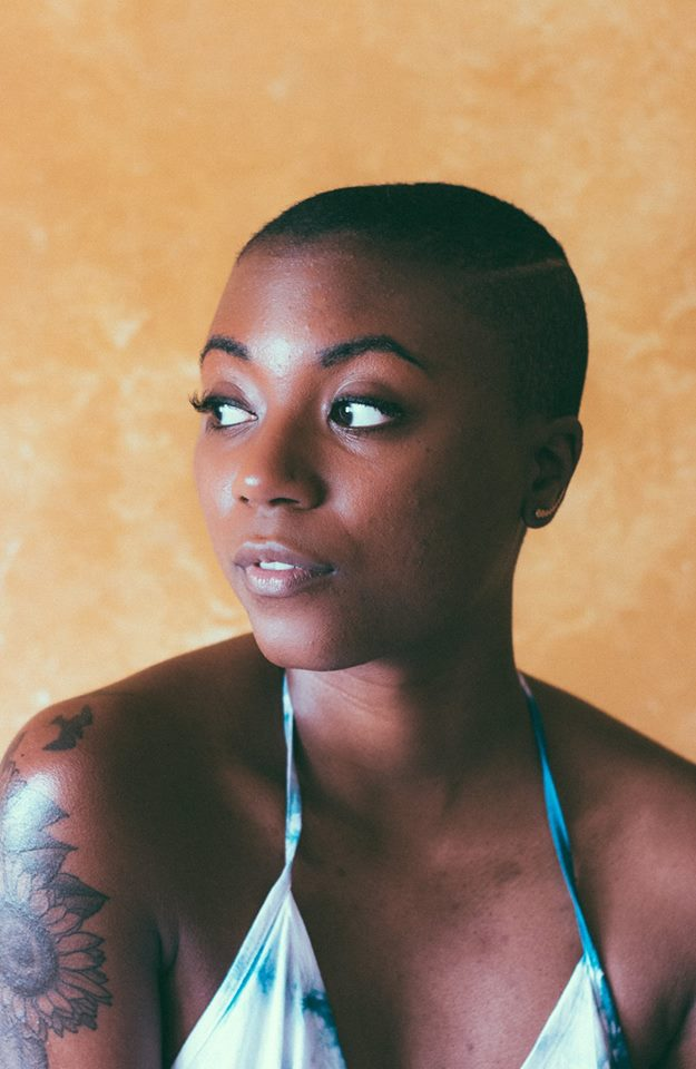 black-woman-arm-tattoo-orange-background.jpg
