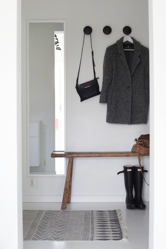 seating in an entryway is pretty well a no-brainer. how nice to be able to take a seat to put your shoes on (especially in our long edmonton winters where bundling up is a must) i also am loving the white framed mirror on the white wall, less busy looking, and opens up the small space. and as well as mirrors looking incredible incorporated into design, it's nice to have the vertical mirror to take one last peak and yourself before you head out. another thing i'm drawn to are the coat/accessory hangers. they add some colour and great functionality for those every day items.