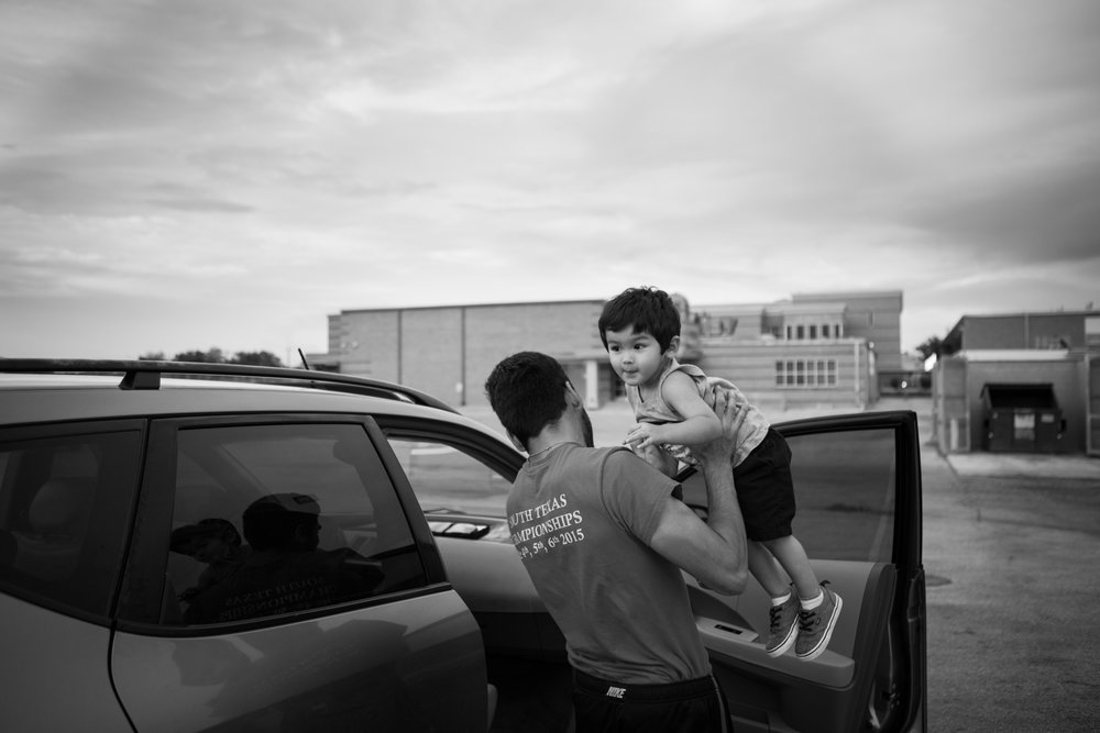 13 July 2017, San Antonio, TX – Jimmy Martinez lifts Jimmy, 2, out of the car to spend the evening at the track at Thomas Edison High School. (Copyright Bonnie Arbittier)