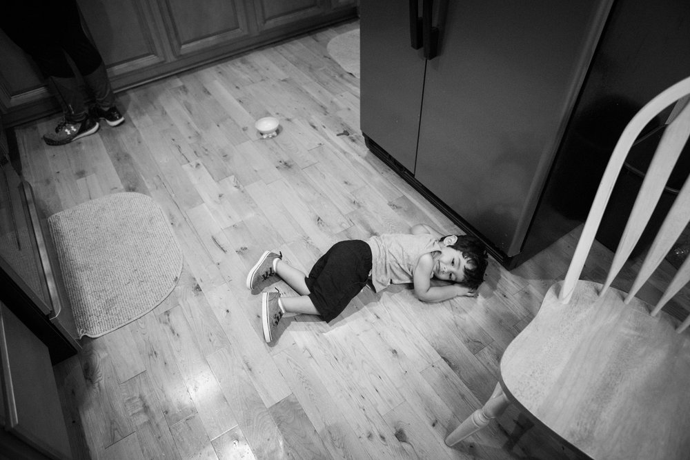 13 July 2017, San Antonio, TX – Jimmy, 2, lies on the kitchen floor as his mother and father make dinner. (Copyright Bonnie Arbittier)