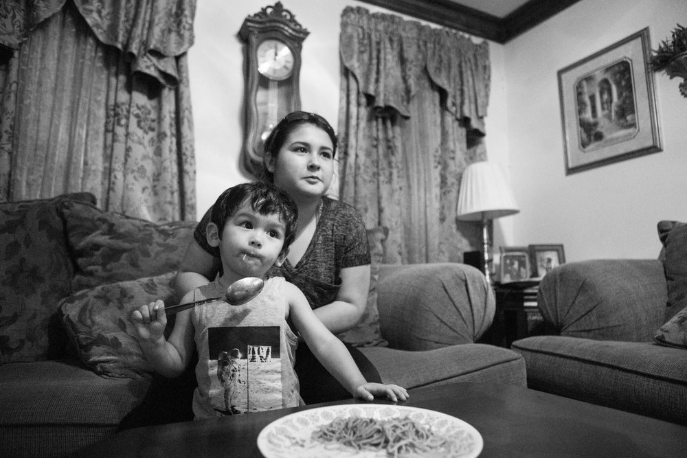 13 July 2017, San Antonio, TX – Alaska Martinez sits with Jimmy, 2, in front of the television as Jimmy eats spaghetti. (Copyright Bonnie Arbittier)