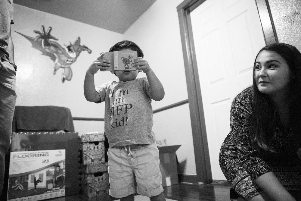 "12 July 2017, San Antonio, TX – Jimmy, 2, ""reads"" his favorite book to his mother Alaska Martinez. (Copyright Bonnie Arbittier)"