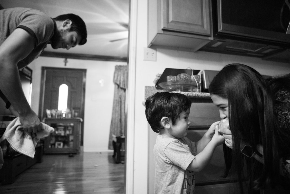 12 July 2017, San Antonio, TX – Jimmy, 2, (center) feeds his mother Alaska Martinez a pear as his father Jimmy Martinez cleans up his spit from the floor. (Copyright Bonnie Arbittier)