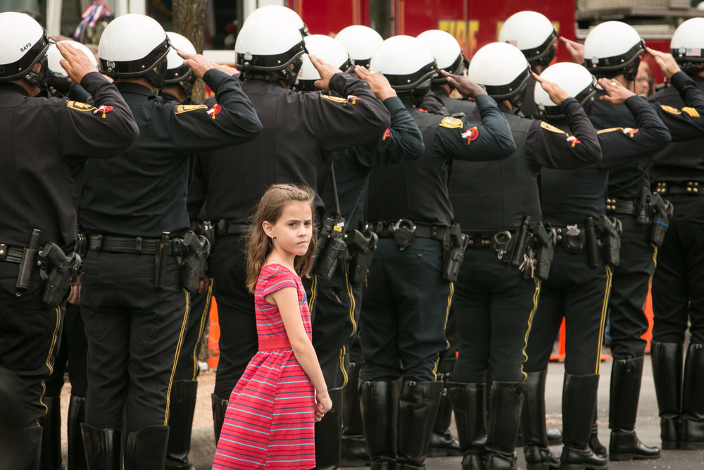 26 May 2016, San Antonio, TX – A young girl listens to a trumpet playing TAPS before the funeral of fallen San Antonio firefighter Scott Deem. (Copyright Bonnie Arbittier)