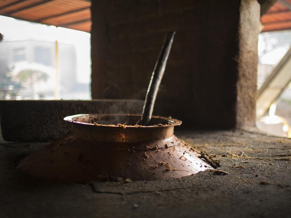 DESTILACIÓN La masa fermentada pasa a un alambique donde se calienta, ebulle y los vapores se condensan en alcohol. Nuestro mezcal se destila dos veces.
