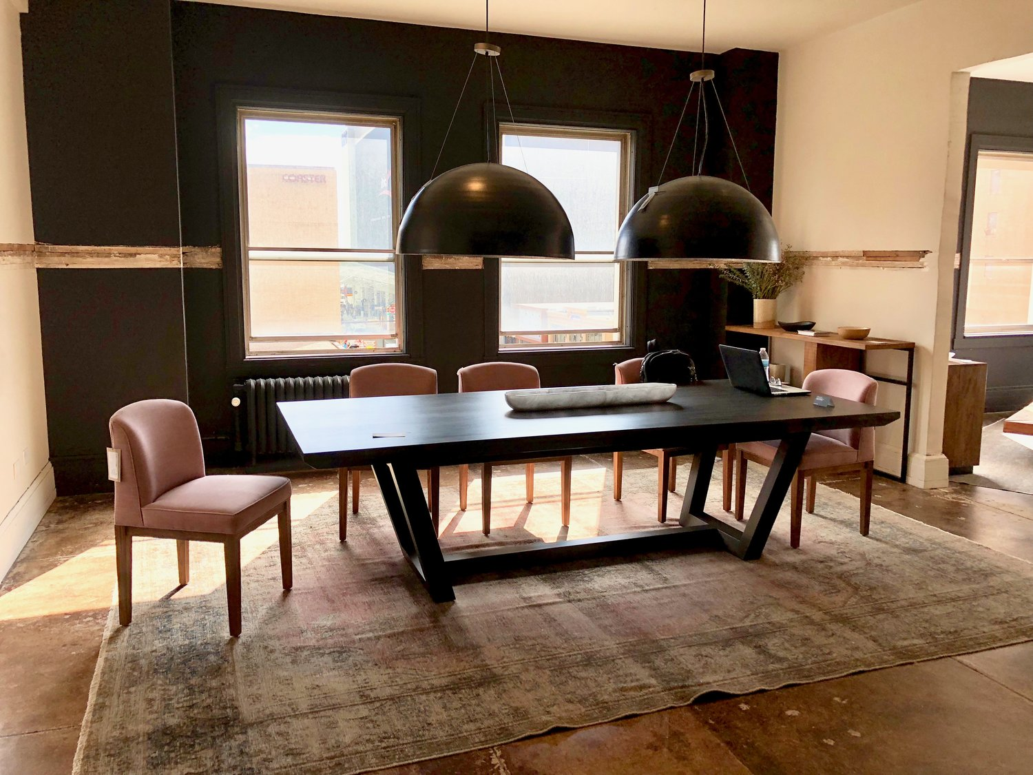 A gorgeous hardwood dining table by Cisco Brothers | Environment paired with pink custom Fasano dining chairs -- you can select from an assortment of beautiful organic cottons & linens, velvets, leather, and mohair.  The table finish and length can be specified as well!
