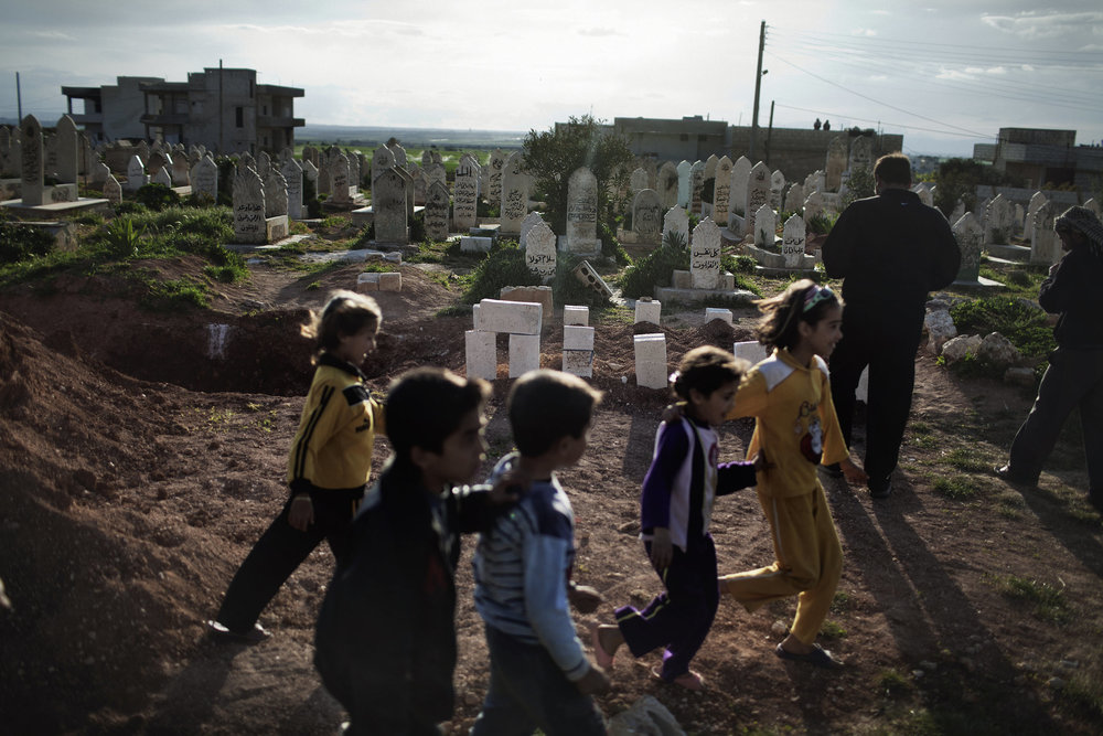 Children skip past a mass grave of victims of the massacre in Taftanaz.