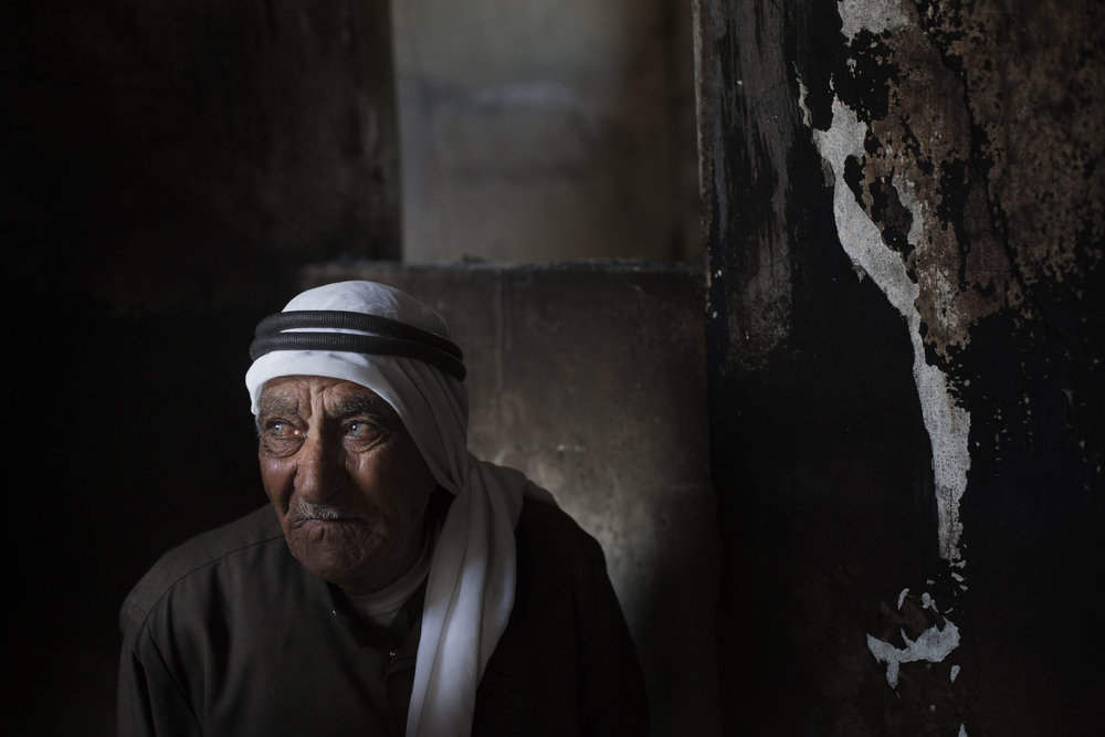 Ahmed Ghonim, 87, stands in the burnt home where his son, Mustafa was killed, Taftanaz.