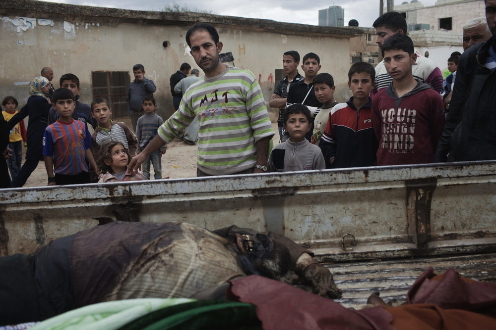 Friends and neighbors look over the body of Jamil Setoot, killed by the Syrian army, Taftanaz.