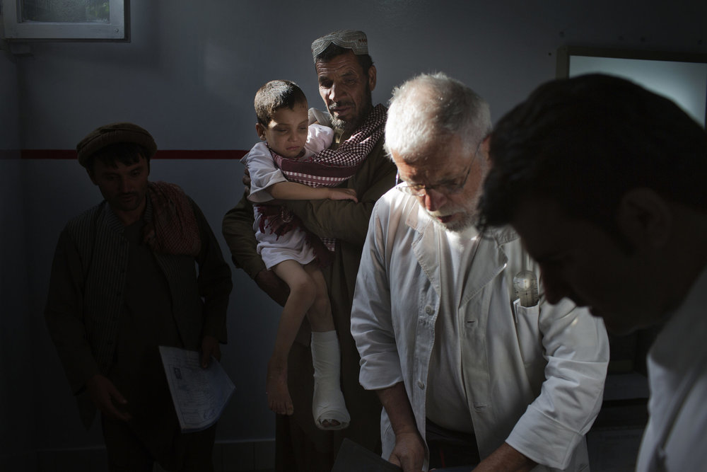 Yasef Naem, 6, is held by his father after an exam by Dr. Alberto Landini.