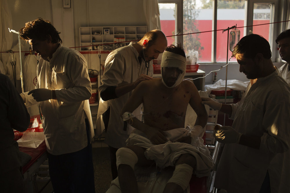 Surgeon Daniel Scerrati, center, examines Jamat Gul, 28, who suffered shrapnel injuries in an IED blast