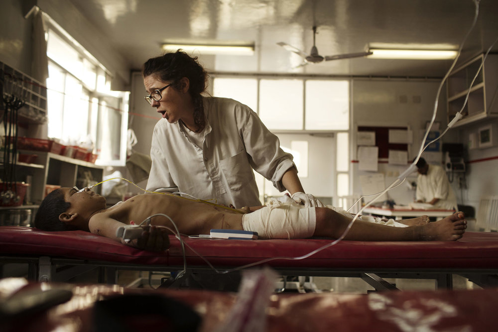 Nurse Georgia Novello comforts Hakim Jan, 10, victim of multiple shell injuries.