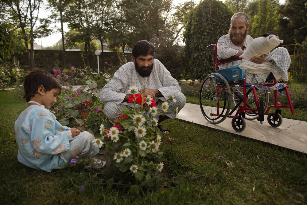 Noor Pacha sits in the garden with his injured son Noorullah, 7, and fellow patient Ab Ahad.