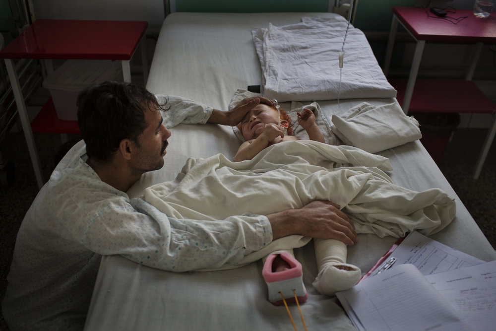 Abdullah, 8 months old, cries as his uncle comforts him the day after a mine explosion that broke both of his legs killed his mother and father.