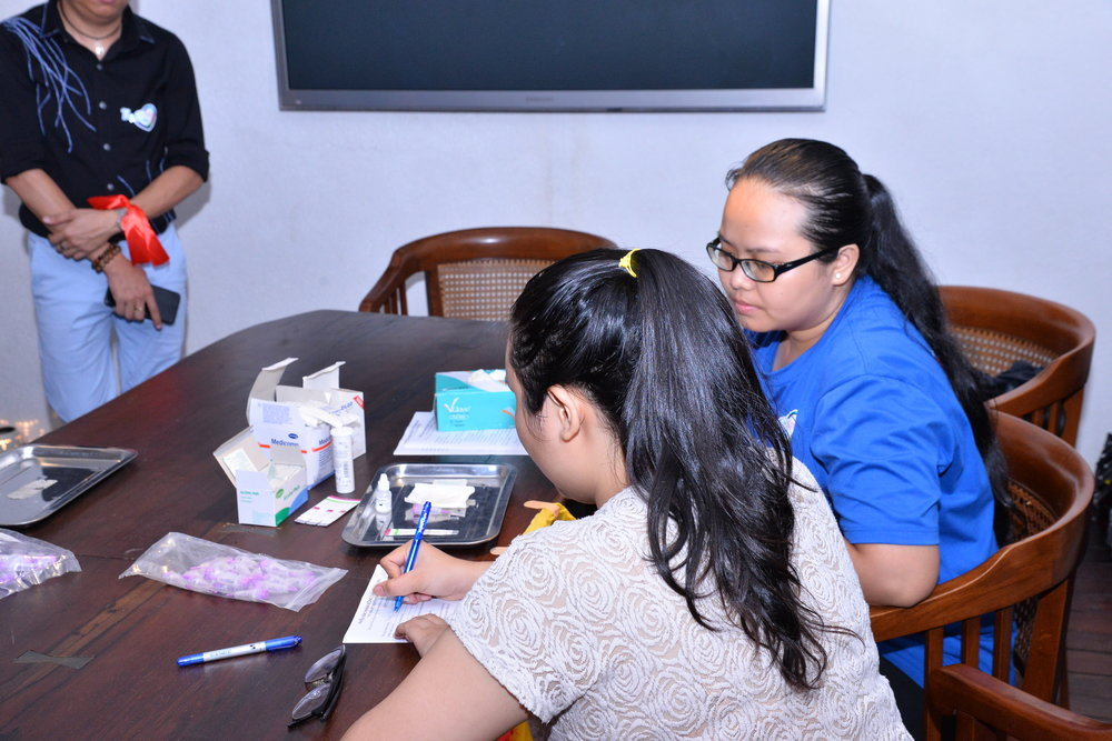 Community-based supporter counsels an event participant on HIV lay testing