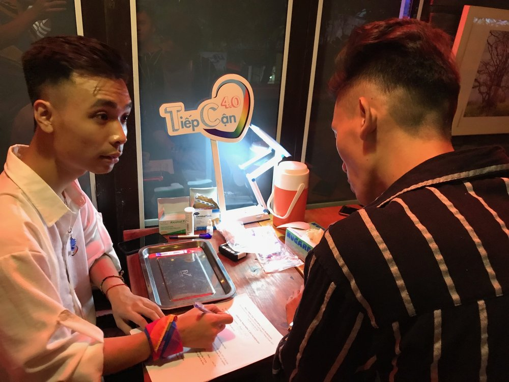 Community-based supporter works with attendee to complete a pre-HIV testing questionnaire at event in Hanoi on September 22