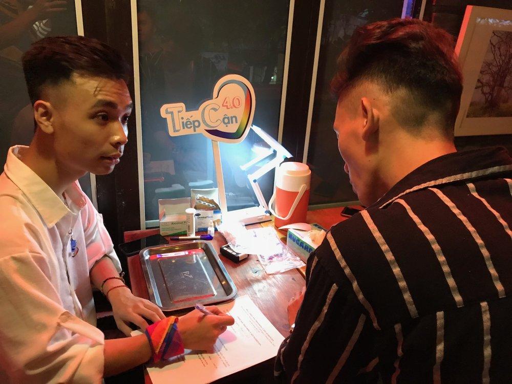 Một hỗ trợ viên cộng đồng đang giúp người tham dự sự kiện hoàn thiện bảng câu hỏi tiền xét nghiệm HIV tại sự kiện diễn ra ở Hà Nội ngày 22/9