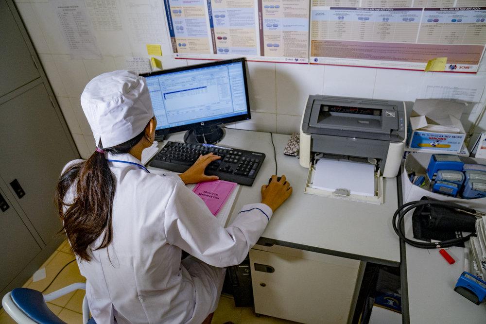 Một nhân viên y tế đang sử dụng hệ thống thông tin y tế được tích hợp để đối chiếu thông tin điều trị và tình trạng sức khỏe của bệnh nhân.