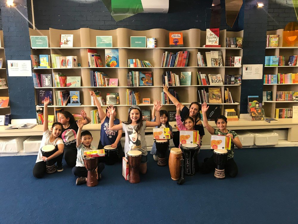 Drumming and dancing workshop with happy children during school holiday programming, led by Antonia Escobar (rear)