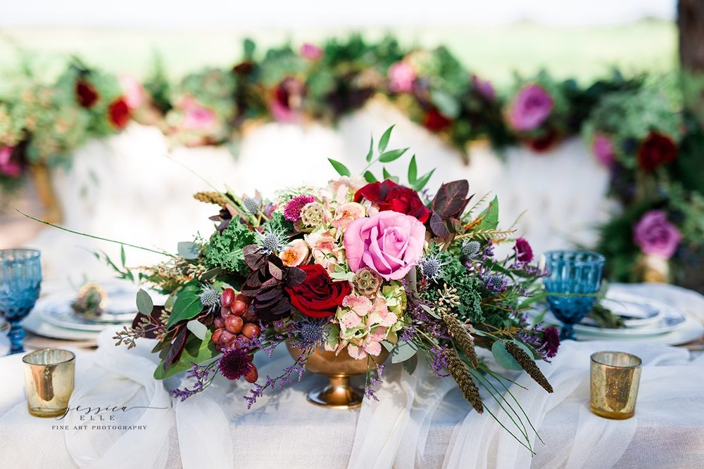 A close up of the floral centerpieces. The grapes added such a raw and unique touch. Photo Credit:  Jessica Elle Photography