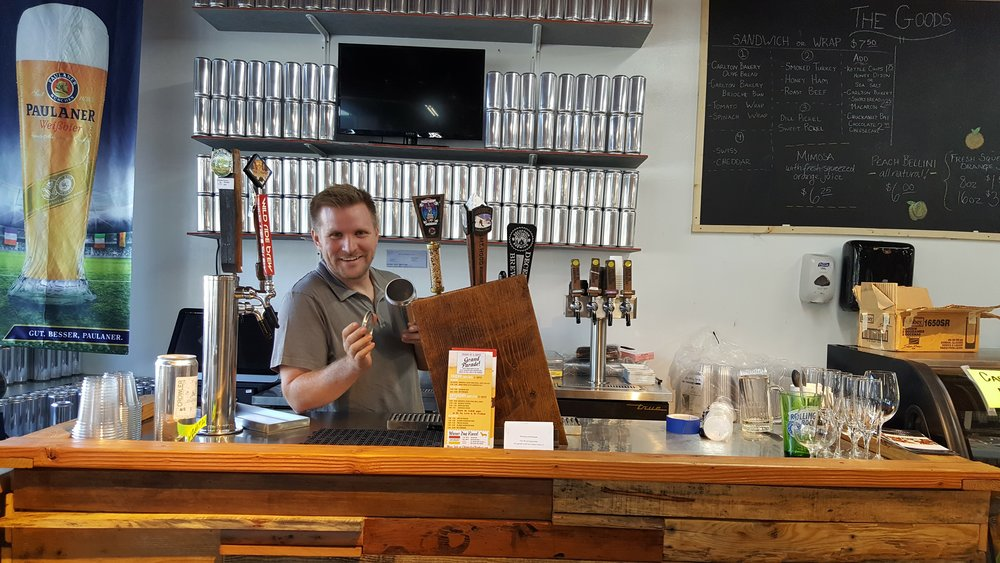 Owner Danny Sikkens of Social Goods behind the Crowler Bar.  A Crowler is a modification of a Growler, in aluminum form allowing the beer to shine.