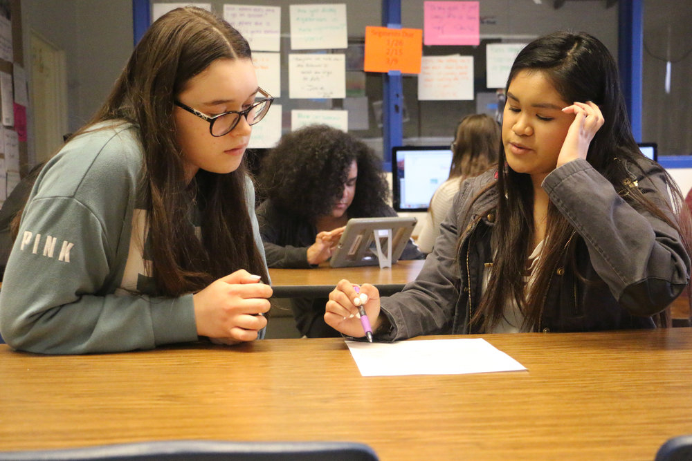 Wheeling High School senior Shailah Magallon (right) works alongside freshman Kamila Walus to help edit a story for the school's newspaper, The Spokesman.