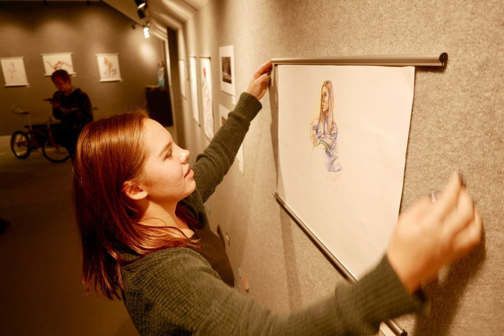 buffalo grove junior emily miksta hangs art in the one grove gallery. this year, students are hoping to start a dialogue around environmental issues through art.