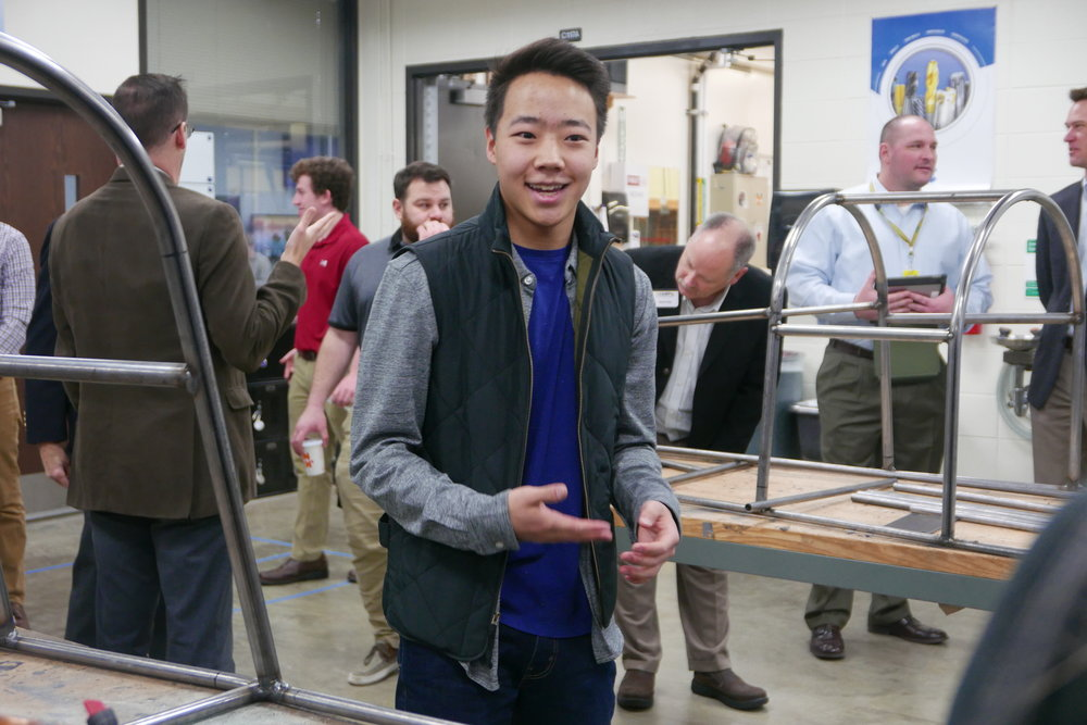 Rolling Meadows junior Quinn Robinson gives a tour of the school's manufacturing and engineering facility at a recent site visit.