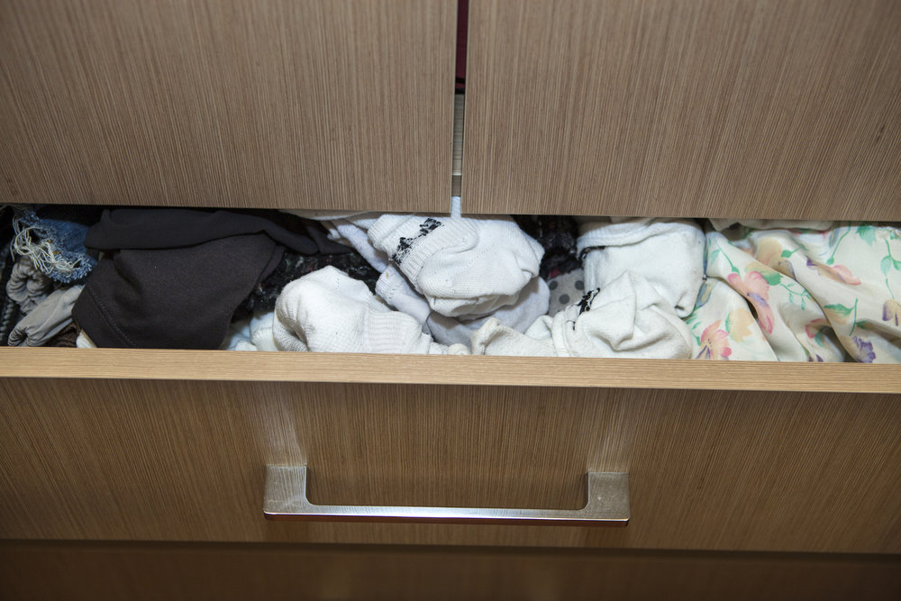 Underwear, socks and pajamas tend to become clutter bombs over the years we store them. Designate a spot for them that's out of sight but easy to access—a custom closet drawer works well. Then, edit your collection down to only what you enjoy wearing and can store neatly.